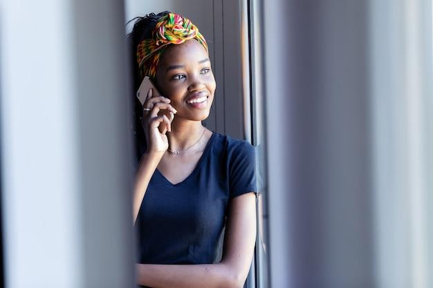 Shot van een mooie jonge vrouw die op een mobiele telefoon praat terwijl ze thuis door het raam kijkt.