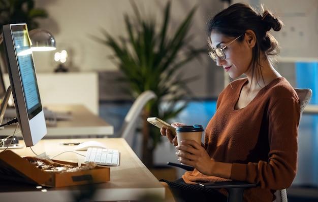 Shot van een mooie jonge zakenvrouw die berichten verzendt met een mobiele telefoon tijdens het werken met een computer op kantoor.