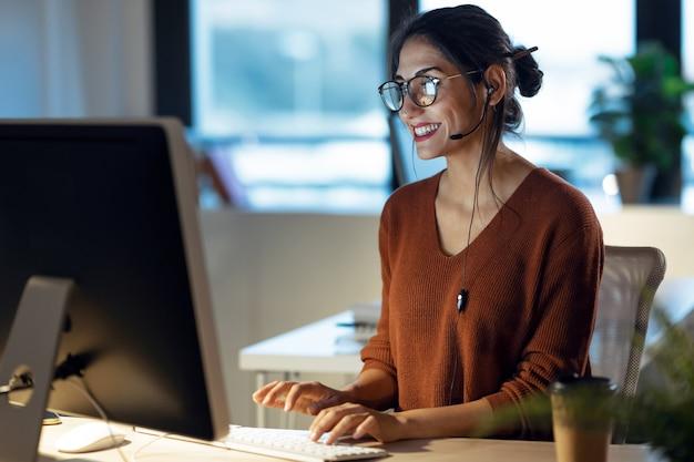 Shot van een mooie jonge zakenvrouw die met de computer werkt terwijl ze met een koptelefoon op kantoor praat.