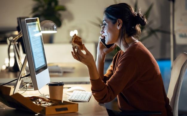 Shot van een mooie jonge zakenvrouw die met de computer werkt terwijl ze pizza op kantoor eet.