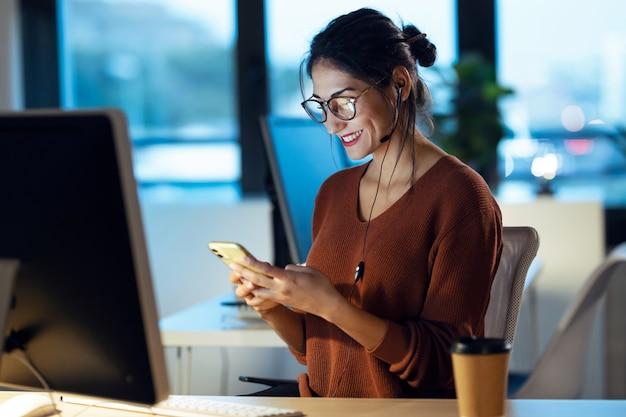 Shot van een mooie jonge zakenvrouw die videogesprek heeft met een mobiele telefoon terwijl ze met een computer op kantoor werkt.
