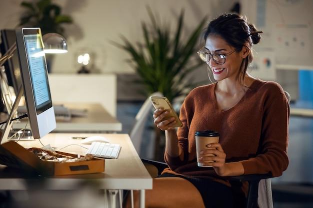 Shot van een mooie jonge zakenvrouw die videogesprek heeft met een mobiele telefoon tijdens het werken met een computer op kantoor.