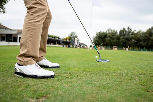 Shot van een onherkenbare golfer die golf speelt op de baan.