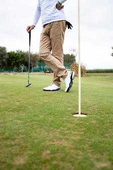 Shot van een onherkenbare golfer die op de golfbaan staat.