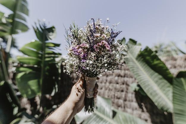 Shot van een persoon met een bruidsboeket en grote groene bladeren op de achtergrond