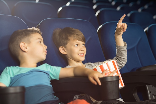 Shot van een schattige kleine jongen die naar het scherm in de bioscoop wijst en iets laat zien aan zijn kleine vrienden.