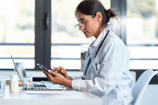Shot van een serieuze vrouwelijke arts die haar smartphone gebruikt tijdens het werken met een laptop in het overleg.