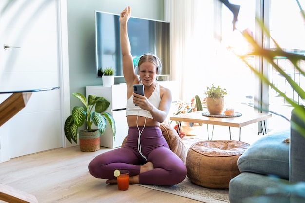 Shot van een sportieve gelukkige vrouw die plezier heeft met het doen van oefeningen terwijl ze naar muziek luistert met een koptelefoon in de woonkamer thuis.