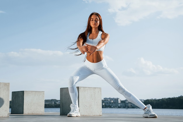 Shot van een sportieve vrouw die overdag fitnessoefeningen doet in de buurt van het meer