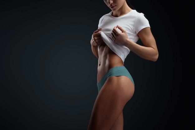 Shot van een sterke vrouw met gespierde buik in sportkleding. jonge vrouw in sportieve lingerie staande op zwarte achtergrond. horizontale bijgesneden studio-opname met kopie ruimte.