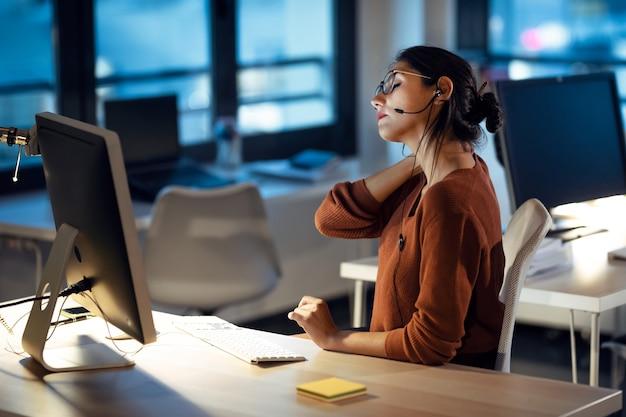 Shot van een vermoeide zakenvrouw met rugpijn die er ongemakkelijk uitziet tijdens het werken met computers op kantoor.