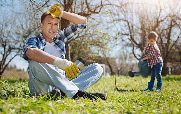 Shot van een volwassen man met een thermoskan, zittend op het gras en rust terwijl zijn zoon een boom op de achtergrond water geeft