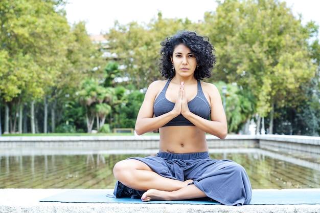 Shot van een vrouw die yoga doet in een park