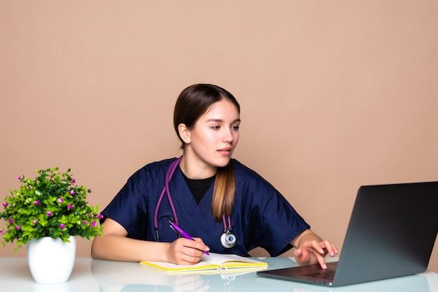 Shot van een vrouwelijke arts die met collega's praat via een videogesprek met een laptop in het consult