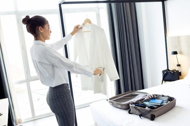 Shot van elegante jonge zakenvrouw in pak haar koffer uitpakken op bed in hotelkamer.