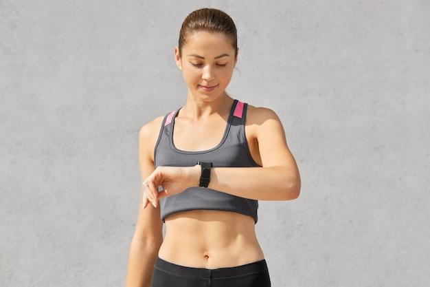 Shot van fitness dame of jogger kijkt aandachtig naar smartwatch, controleert pols en telt calorieën, heeft een gezonde levensstijl