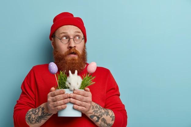 Shot van geïmponeerde peinzende man draait zijn blik opzij, houdt symbolen van de lente en pasen vast, bereidt zich voor op de eierenjacht, draagt een wit konijn in de pot, heeft een verwarde reactie, draagt een rode hoed en een trui.