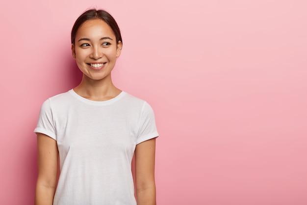 Shot van gelukkige jonge aziatische vrouw heeft tedere glimlach, kijkt opzij met charmante uitdrukking, draagt casual wit t-shirt, heeft natuurlijke schoonheid, geïsoleerd op roze muur. mensen en emoties concept