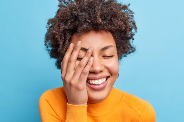 Shot van gelukkige krullende jonge afro-amerikaanse vrouw sluit ogen en grijnst van vreugde houdt handpalm op gezicht drukt authentieke emoties uit geïsoleerd over blauwe muur heeft plezier natuurlijke frisse schone huid