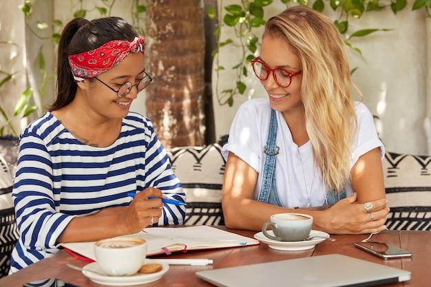 Shot van gemengd ras vrouwen denken over een gemeenschappelijke taak, schrijven ideeën in notitieblok