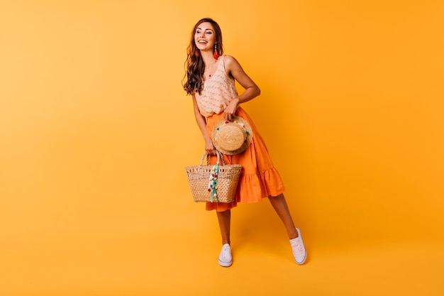 Shot van gemiddelde lengte van geïnspireerde vrouw met zomeraccessoires. gelukkig gember vrouwelijk model in de oranje hoed en zak van de rokholding.