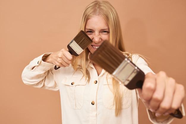 Shot van jonge vrouwelijke huisschilder in uniform poseren geïsoleerd met twee verfborstels in haar handen