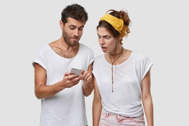 Shot van knappe ongeschoren man toont wat website nieuws aan zijn europese vrouw, houdt mobiele telefoon vast, staat over een witte muur, geniet van supersnel internet op elektronisch apparaat