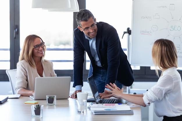 Shot van lachende zakenman praten met collega's in de vergadering over coworking space.