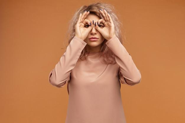 Shot van mooie ernstige jonge vrouw in stijlvolle top met lange mouwen die doet alsof ze verrekijker gebruikt
