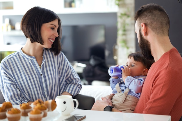 Shot van mooie jonge ouders die naar de baby kijken terwijl hij thuis water drinkt met een zuigfles.