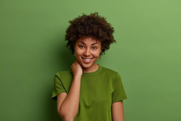 Shot van mooie vrouw met perfecte huid en brede glimlach, raakt nek, in goed humeur, heeft een informeel gesprek, draagt zomer groen t-shirt, vormt binnen. positieve menselijke emoties concept