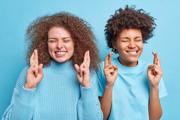 Shot van multi-etnische vrouwen staan naast elkaar kruis vinger voor geluk anticiperen op positief nieuws of resultaat ogen sluiten pose optimistisch drssed terloops geïsoleerd over blauwe muur