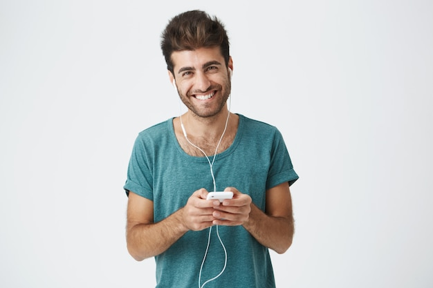 Shot van op zoek gelukkig jongeman breed lachend als hij praat met zijn vriendin tijdens online bellen met oortelefoons en zijn elektronische gadget. mensen, technologie en communicatieconcept