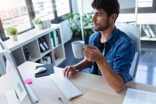 Shot van softwareontwikkelaar die koffie drinkt tijdens het werken met de computer in het moderne opstartkantoor.