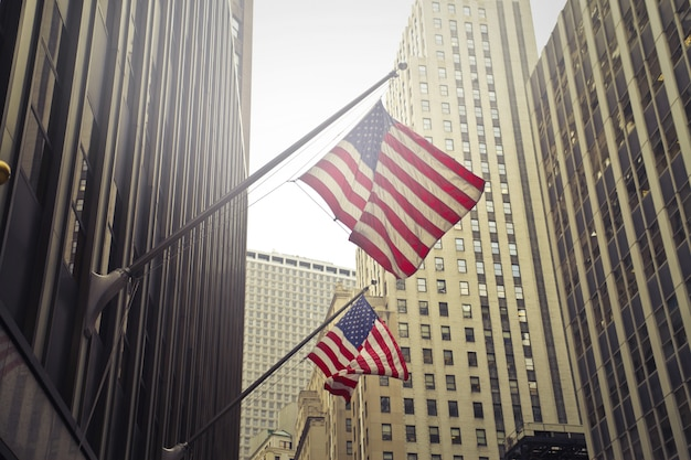 Shot van twee amerikaanse of amerikaanse vlaggen op een hoogbouw