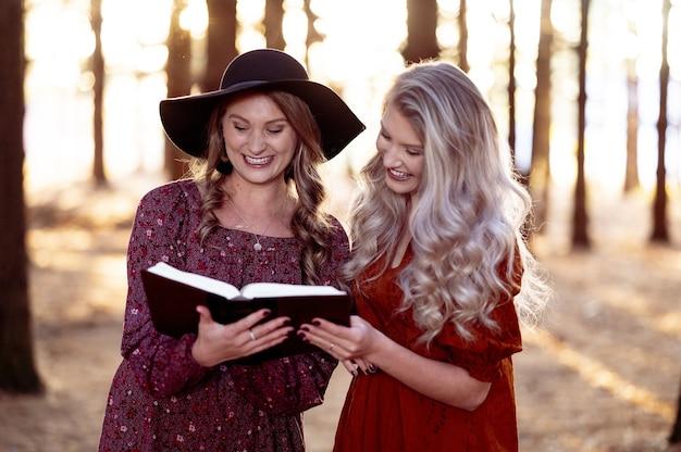 Shot van twee jonge vrouwen poseren met een boek in het bos, herfststemming