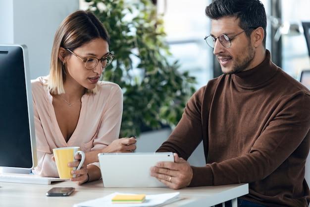 Shot van twee jonge zakelijke collega's die samenwerken met computer een digitale tablet in moderne werkruimte. brainstormconcept.