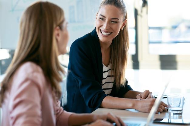 Shot van twee mooie zakenvrouwen die samenwerken met een laptop terwijl ze praten over baannieuws op kantoor.