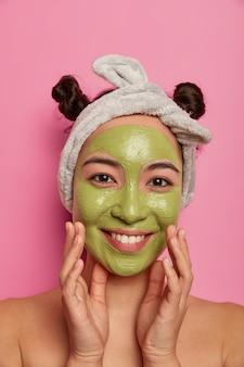 Shot van vrij natuurlijke vrouw raakt wangen zachtjes glimlacht en past schoonheidsmasker toe op gezicht geeft om teint en lichaam staat naakt binnen volgt advies van schoonheidsspecialist hoe acnes te verminderen