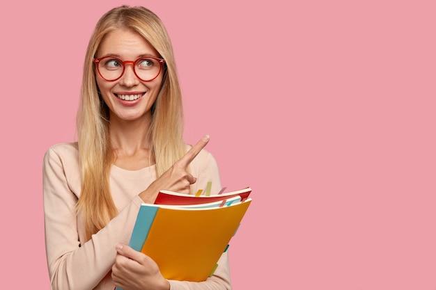 Shot van vrolijk tevreden vrouwelijk model met brede glimlach, draagt een transparante bril