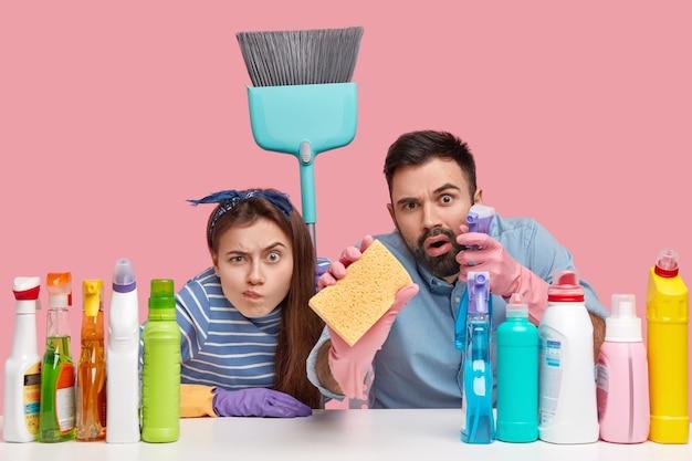Shot van vrouw en man kijken nauwgezet, huishoudelijk werk doen, alles schoonmaken, spons en bezem vasthouden, op de werkplek zitten met wasmiddelen, geïsoleerd over roze muur. huishoudelijke taken