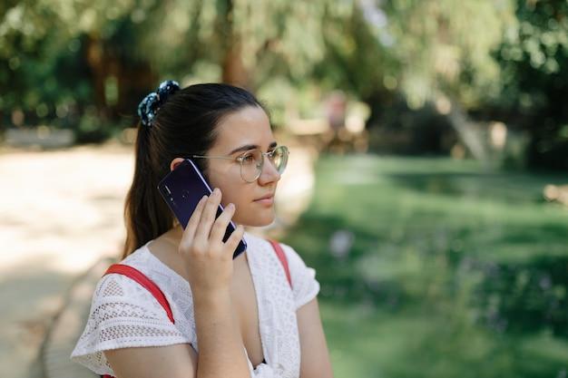 Shot vanuit een gemiddeld perspectief van een jonge vrouw met een witte jurk en een rode rugzak die telefoneert in een park