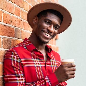 Shot vanuit een gemiddeld perspectief van een man die van een kopje koffie geniet