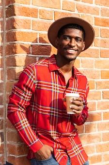 Shot vanuit een gemiddeld perspectief van een man in een rood shirt die koffie drinkt