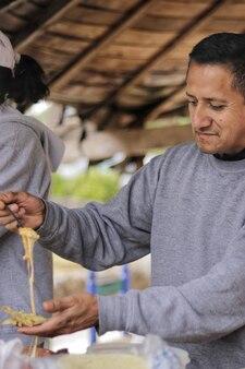 Shot vanuit een gemiddeld perspectief van een vijftigjarige volwassen man die lacht en een taco bereidt met vlees en gesmolten kaas onder een houten kiosk in een grijs sweatshirt