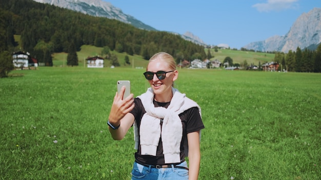Shot vanuit een gemiddeld perspectief van een vrouw die een videogesprek voert vanuit een prachtig natuurpark voor bergen. ze deelt indrukken van haar reis.