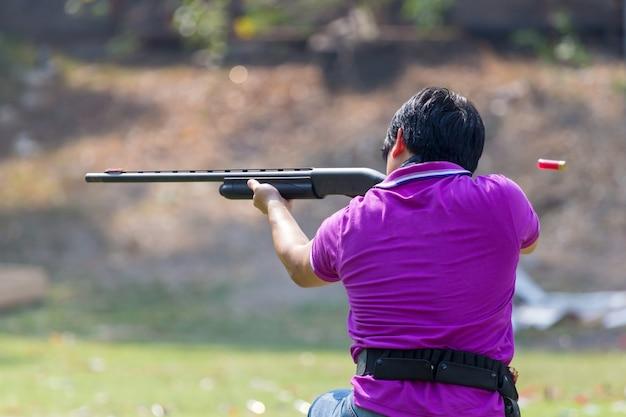 Shoter schieten pistool op een buiten schietbaan, selectieve aandacht