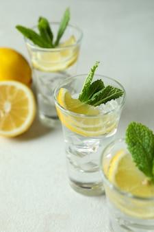 Shots met schijfje citroen en munt op witte geweven tafel