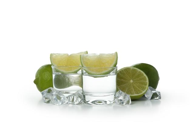 Shots van wodka, limoen en ijsblokjes geïsoleerd op wit