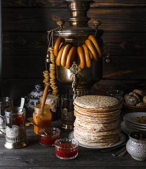 Shrovetide maslenitsa butter week festivalmaaltijd. stapel russische pannenkoeken, samowar